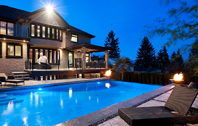 Backyard swimming pool with tiki torches