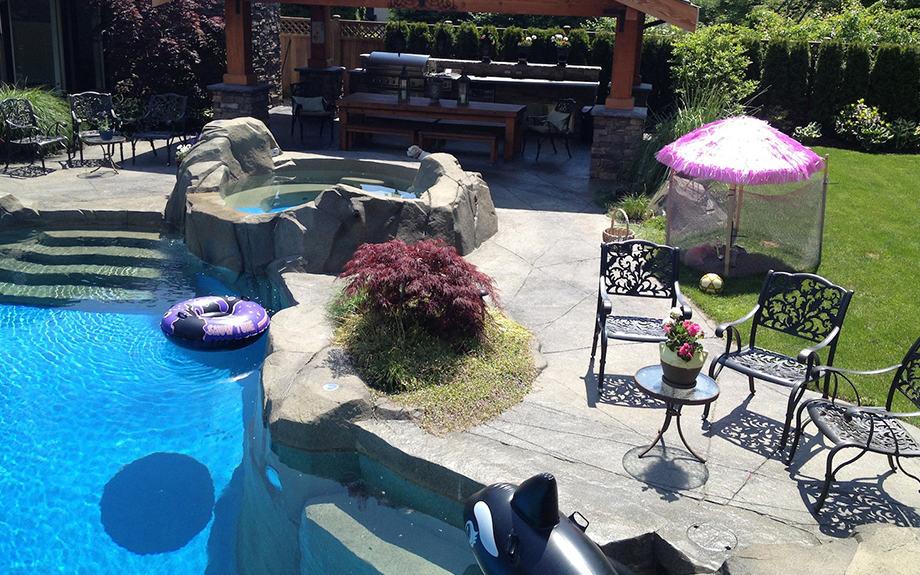 Backyard kitchen, hot tub, and swimming pool
