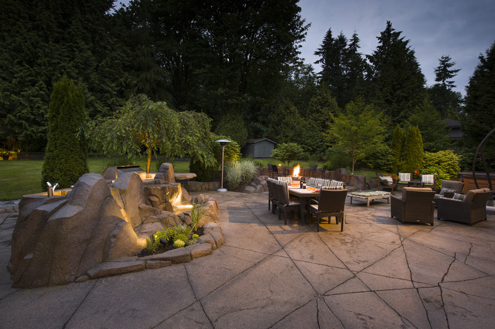 Backlit backyard with custom concrete paving, planters, and dining area