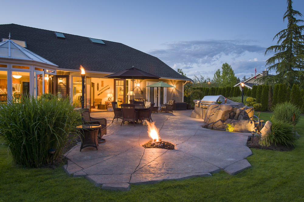 Beautiful backyard design at nighttime with pond and fire pit