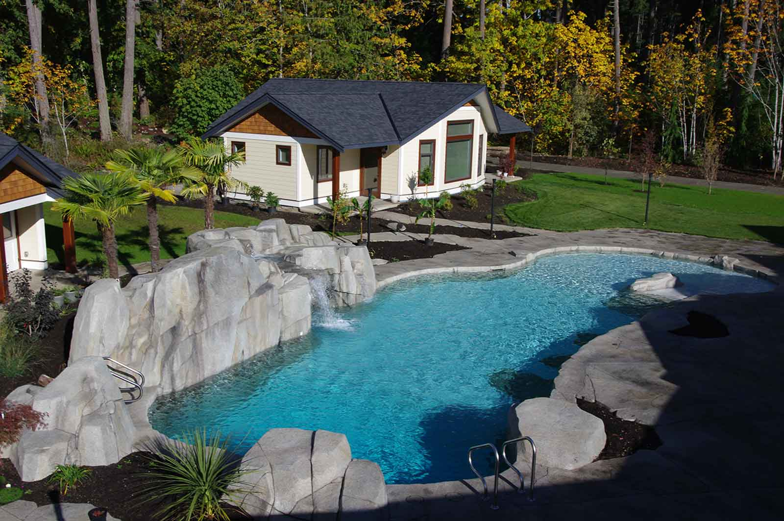 Large custom designed in-ground swimming pool with artificial rock wall