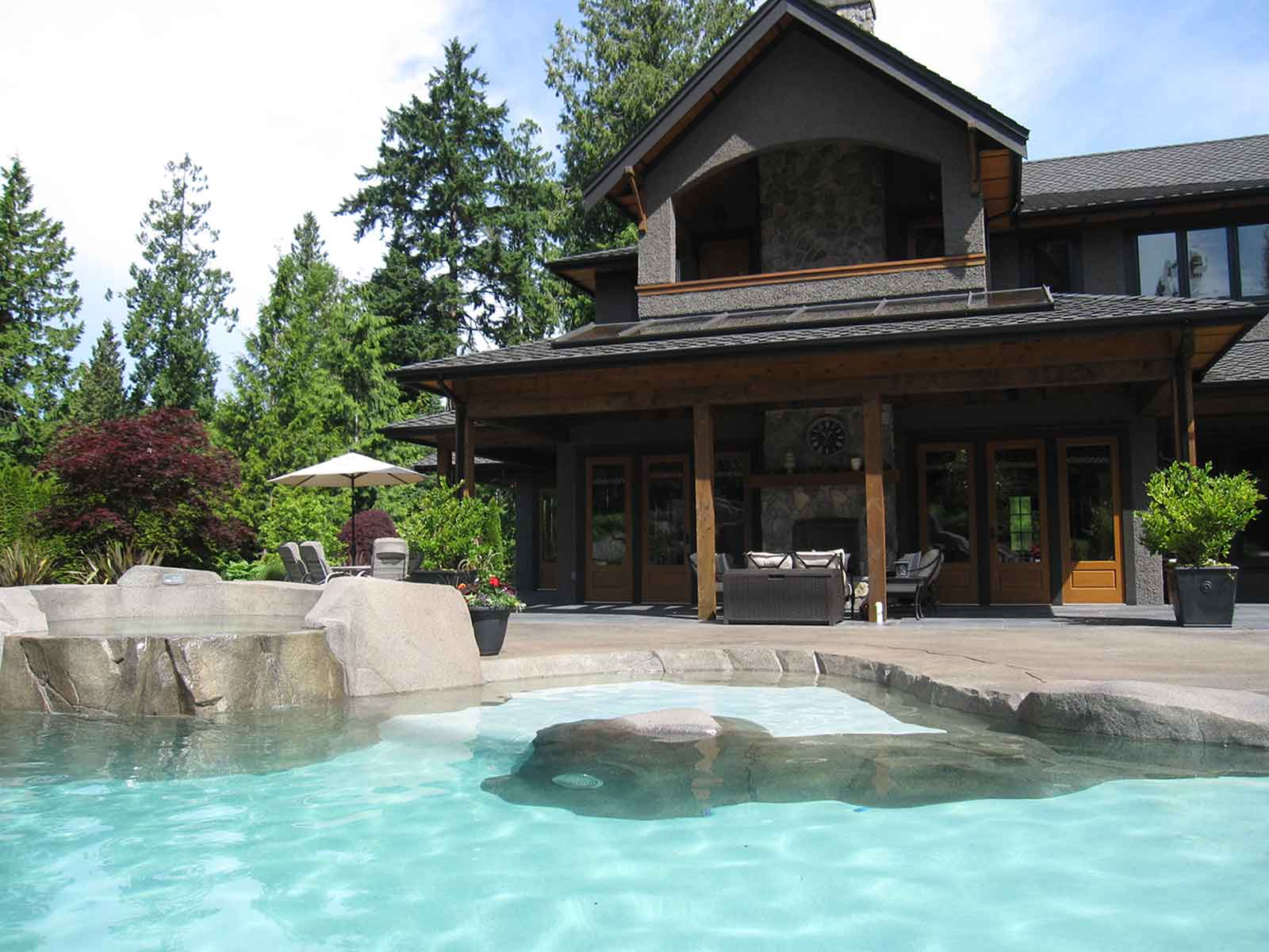Beautiful backyard with custom in-ground swimming pool and sculted rock