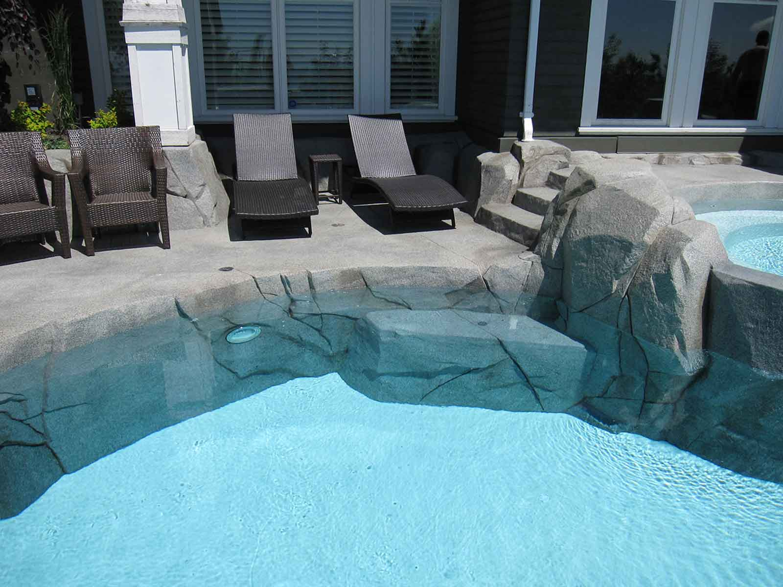 Concrete rock work surrounding in-ground swimming pool
