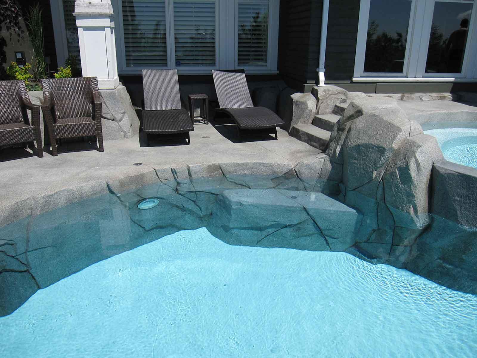 Concrete rock work surrounding in-ground swimming pool