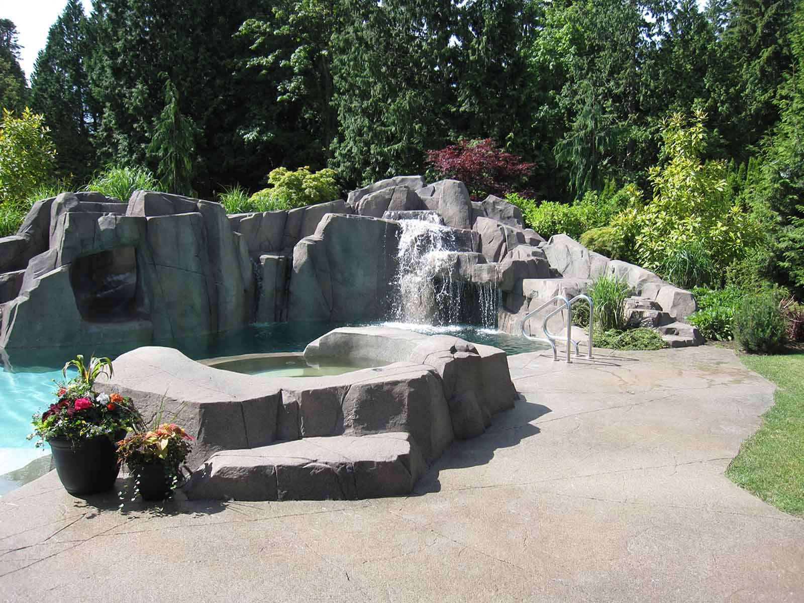 Custom backyard concrete paved patio and pool deck