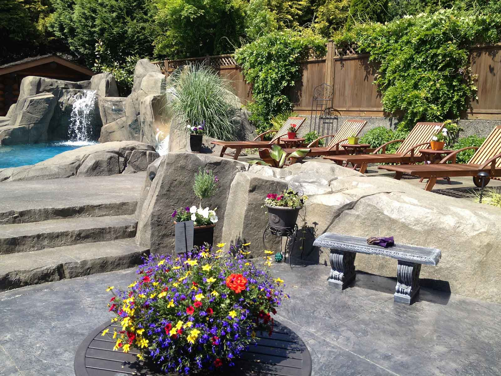 Luxurious backyard with custom concrete paved patio and stairs