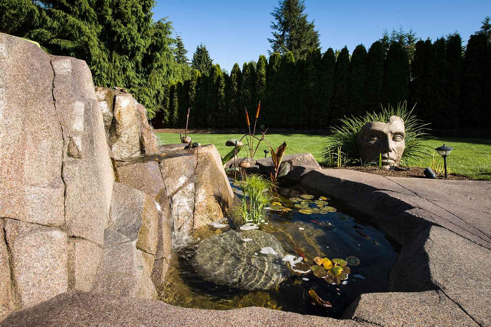 Custom garden pond with concrete rock wall