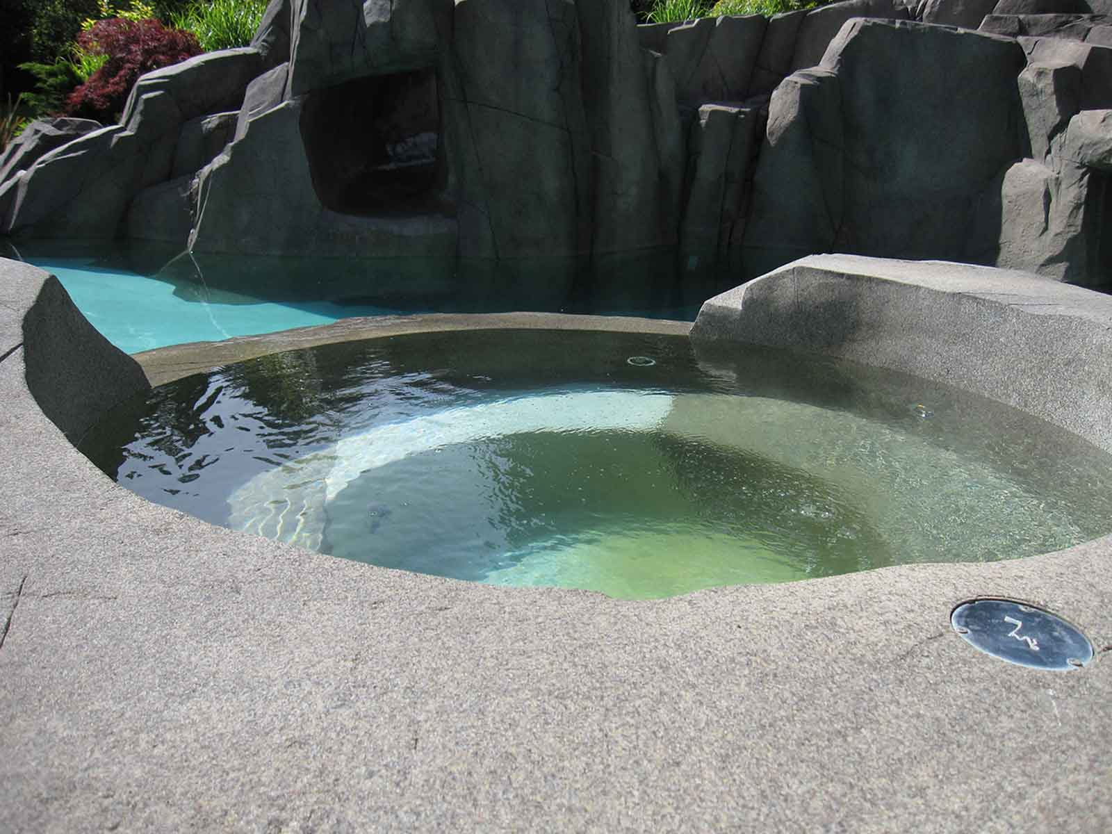 Custom in-ground hot tub with concrete patio