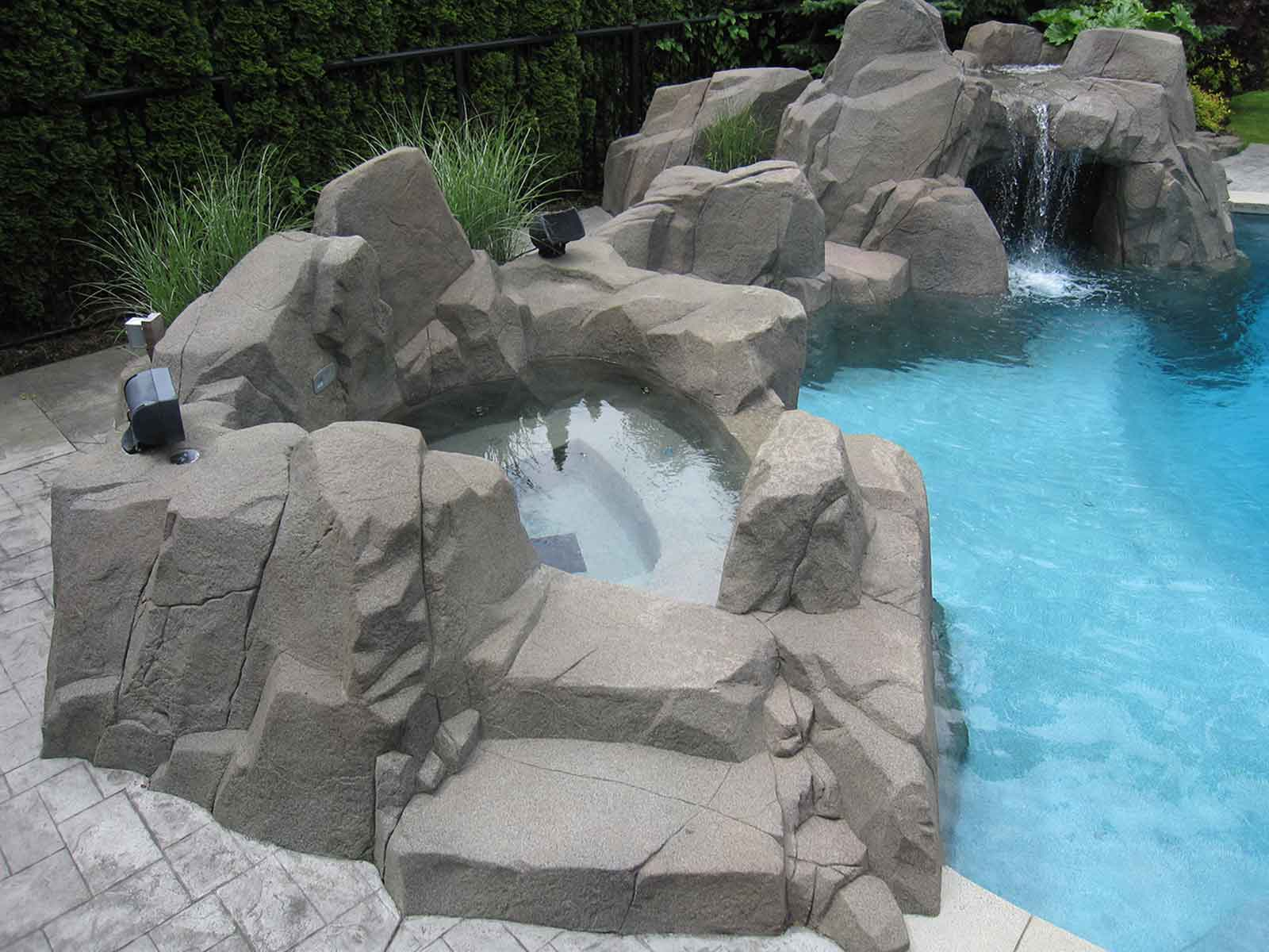 Custom natural looking rock work surrounding swimming pool