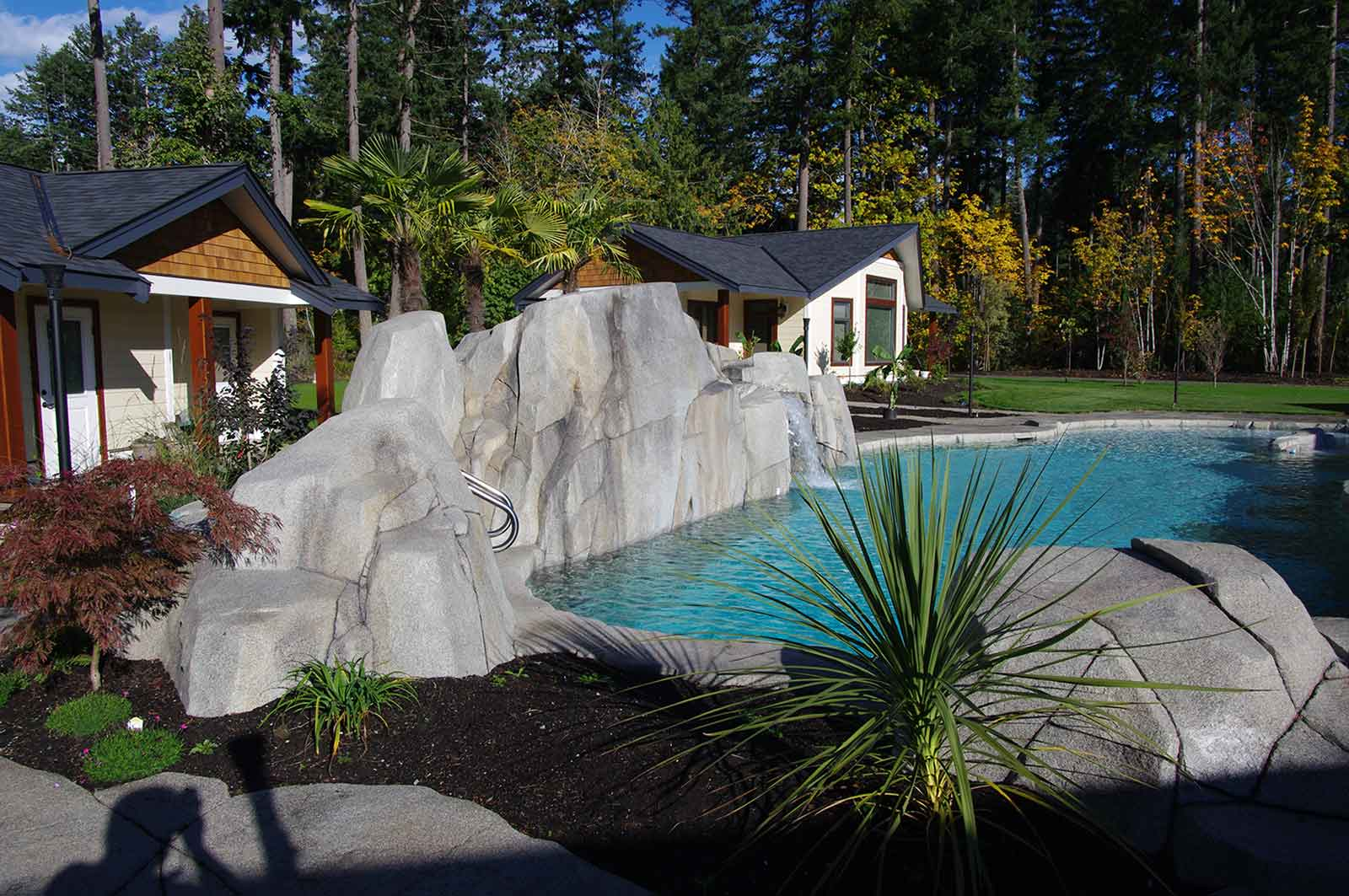 In-ground natural looking swimming pool with artificial rock wall