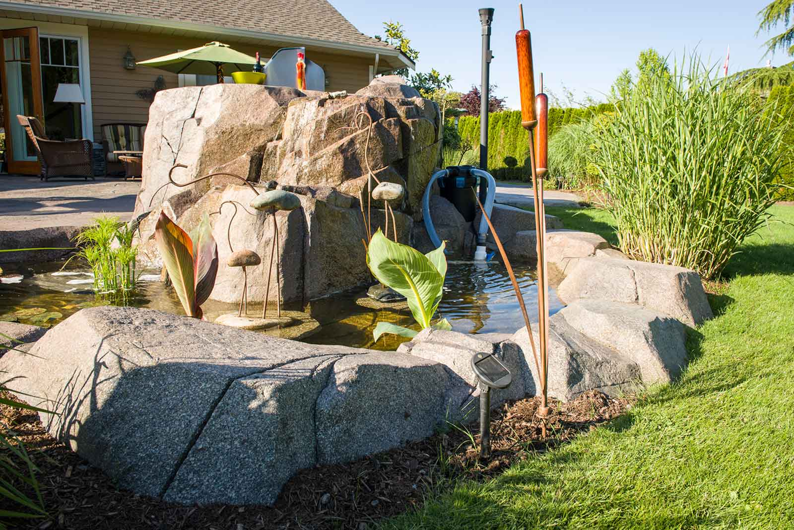 Outdoor custom garden pond with artificial rock wall