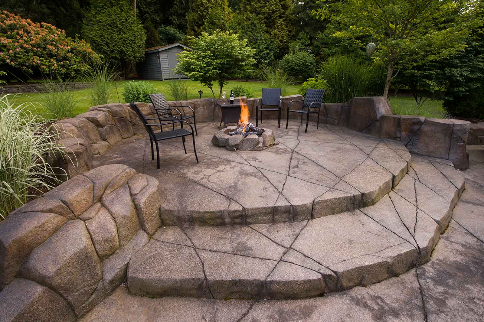 Gas fire pit with custom paved concrete patio and stairs