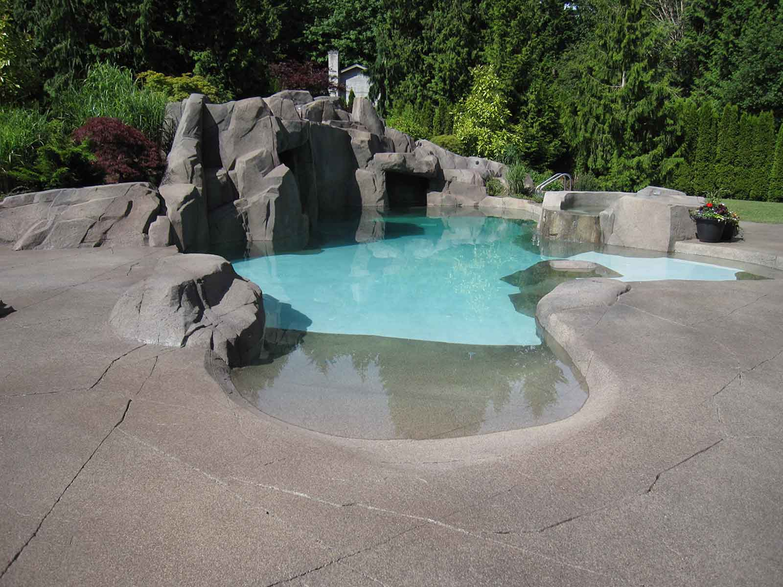 Outdoor swimming pool with artificial rock wall and large patio