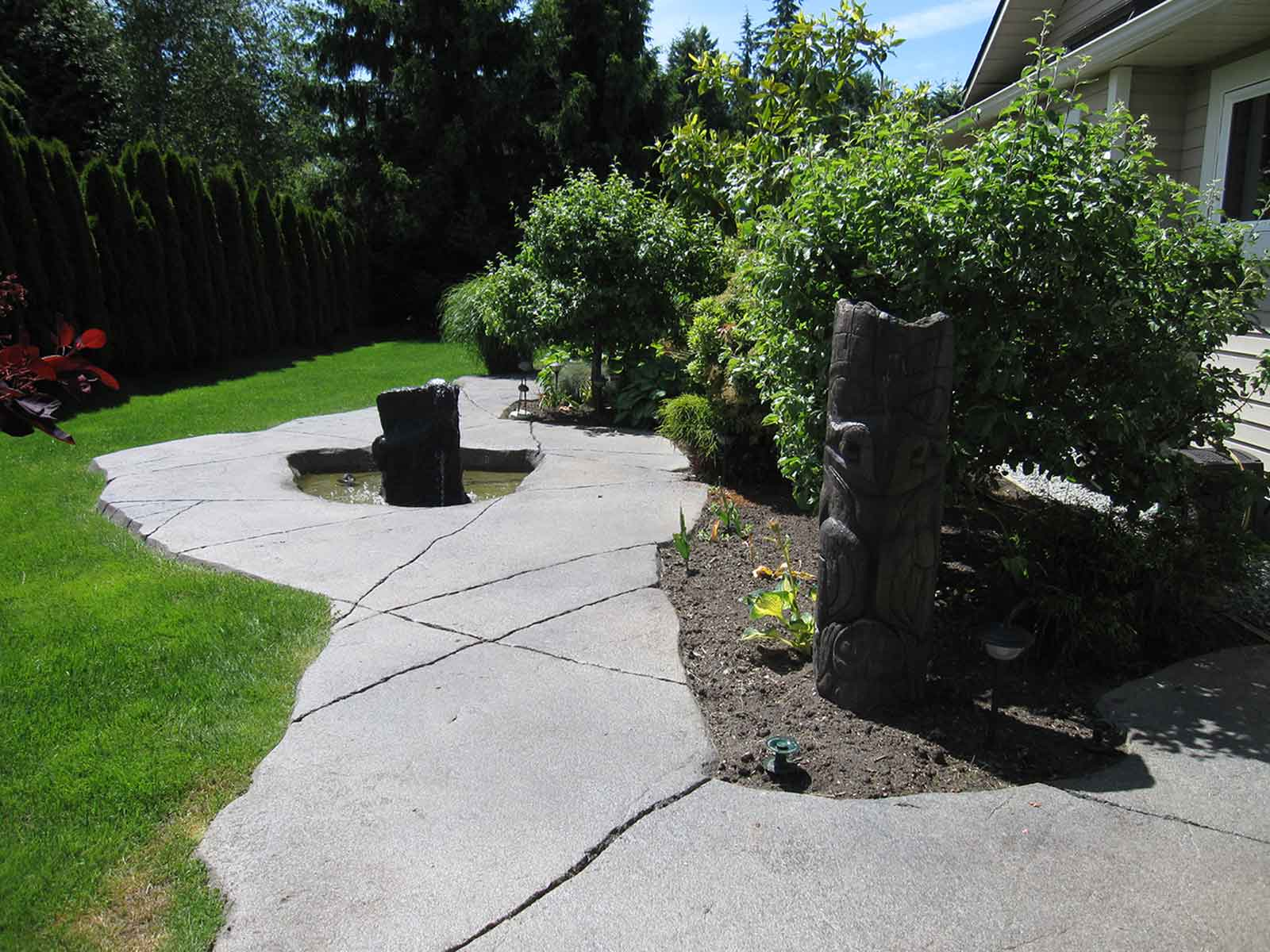 Backyard concrete pathway and pond