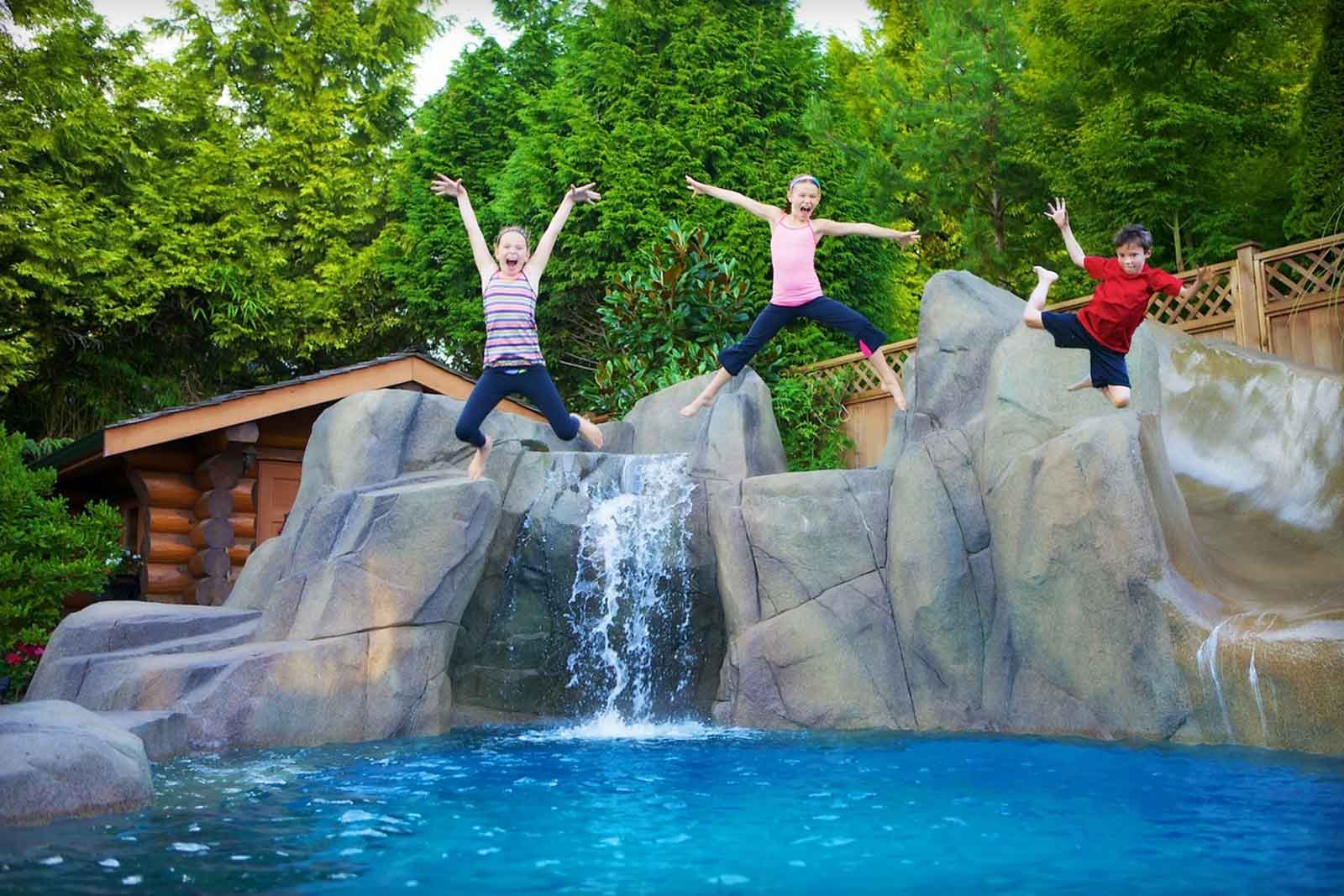 Stunning family backyard waterfall into swimming pool