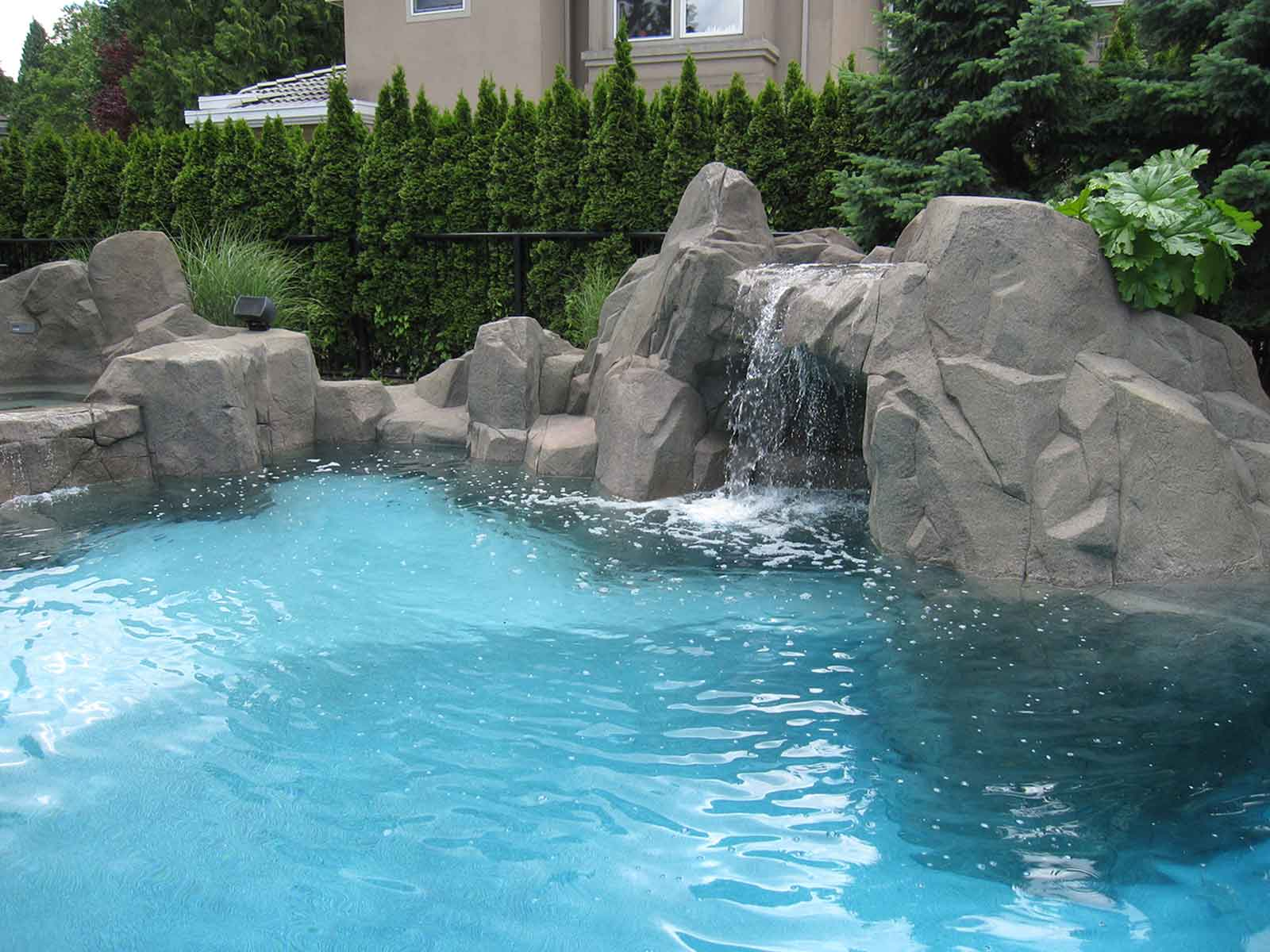 Luxury custom designed swimming pool with artificial rock wall surround
