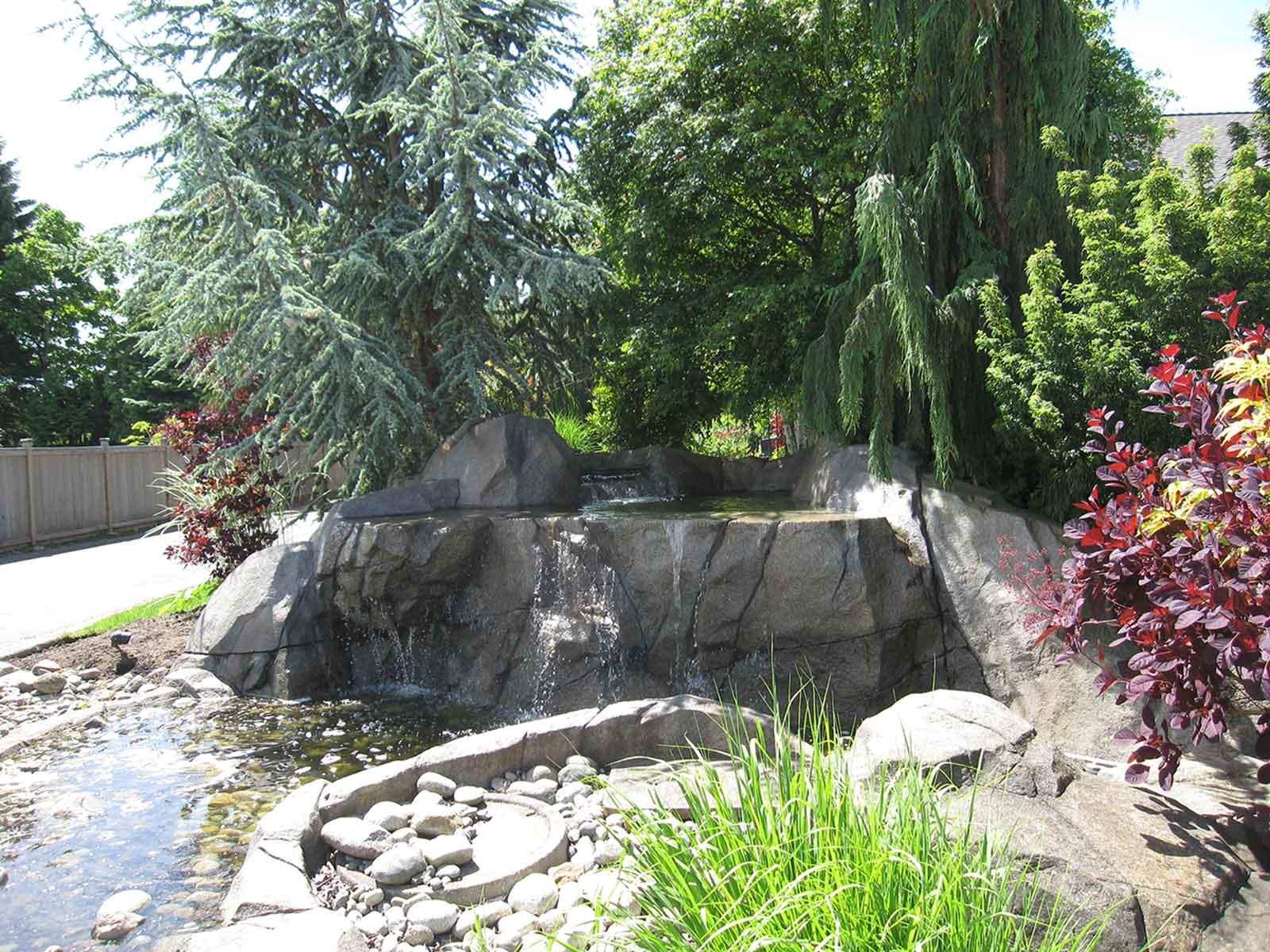 Custom backyard water feature with waterfall