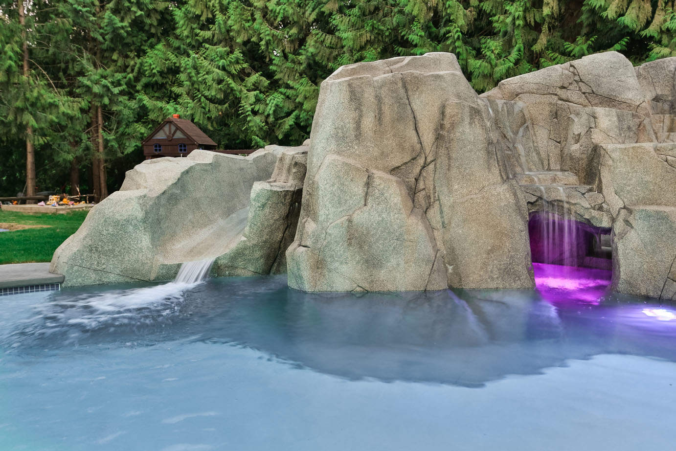 Concrete waterfall feature with swimming pool and colour changing LED swimming pool lights