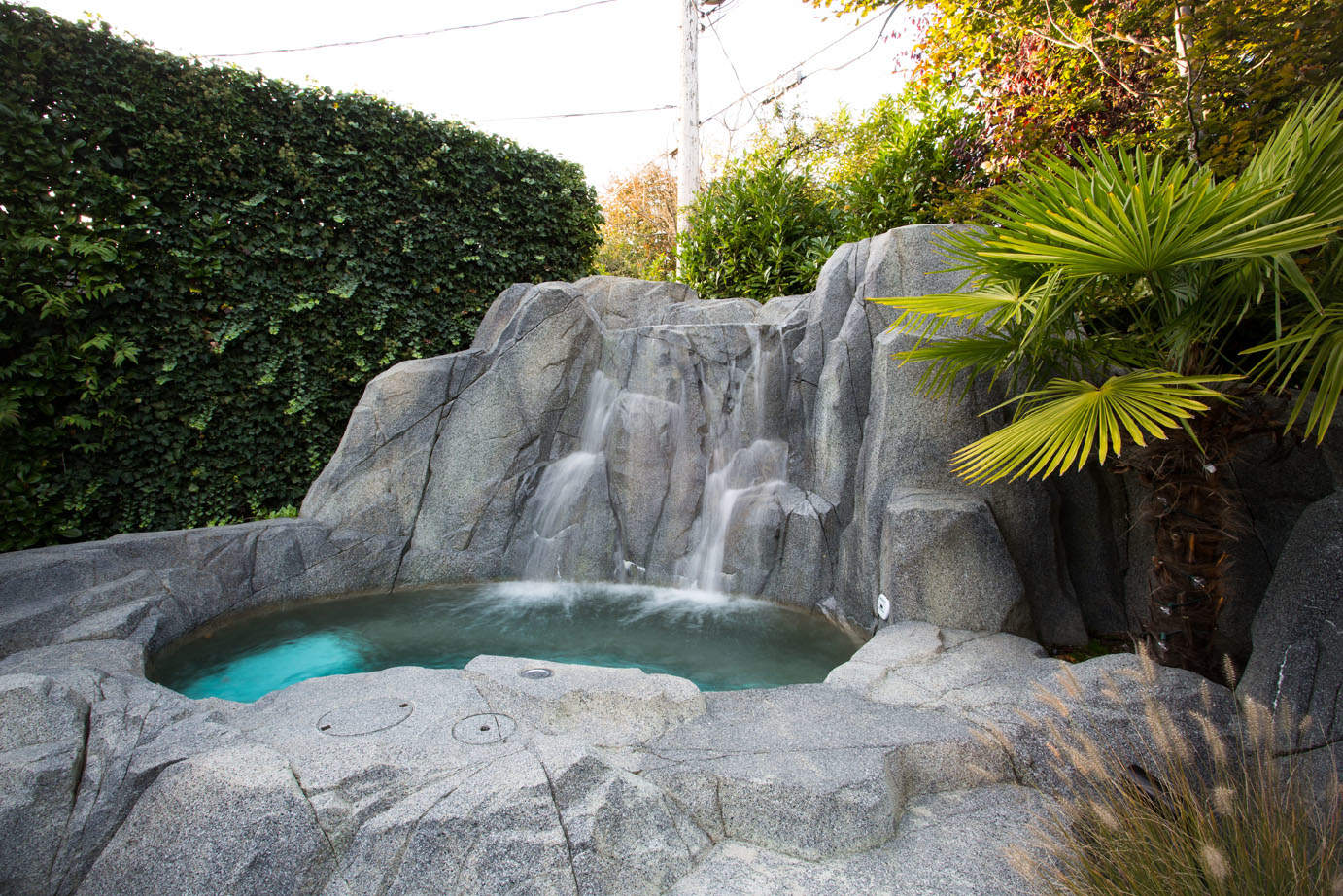 Elegant Custom Concrete Hot Tub With Waterfall Feature