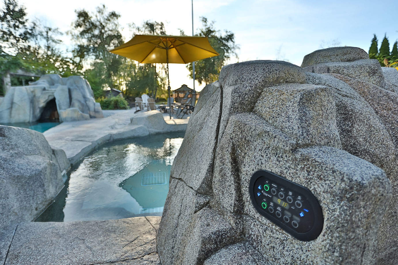 Custom artificial rock work surrounding in-ground swimming pool