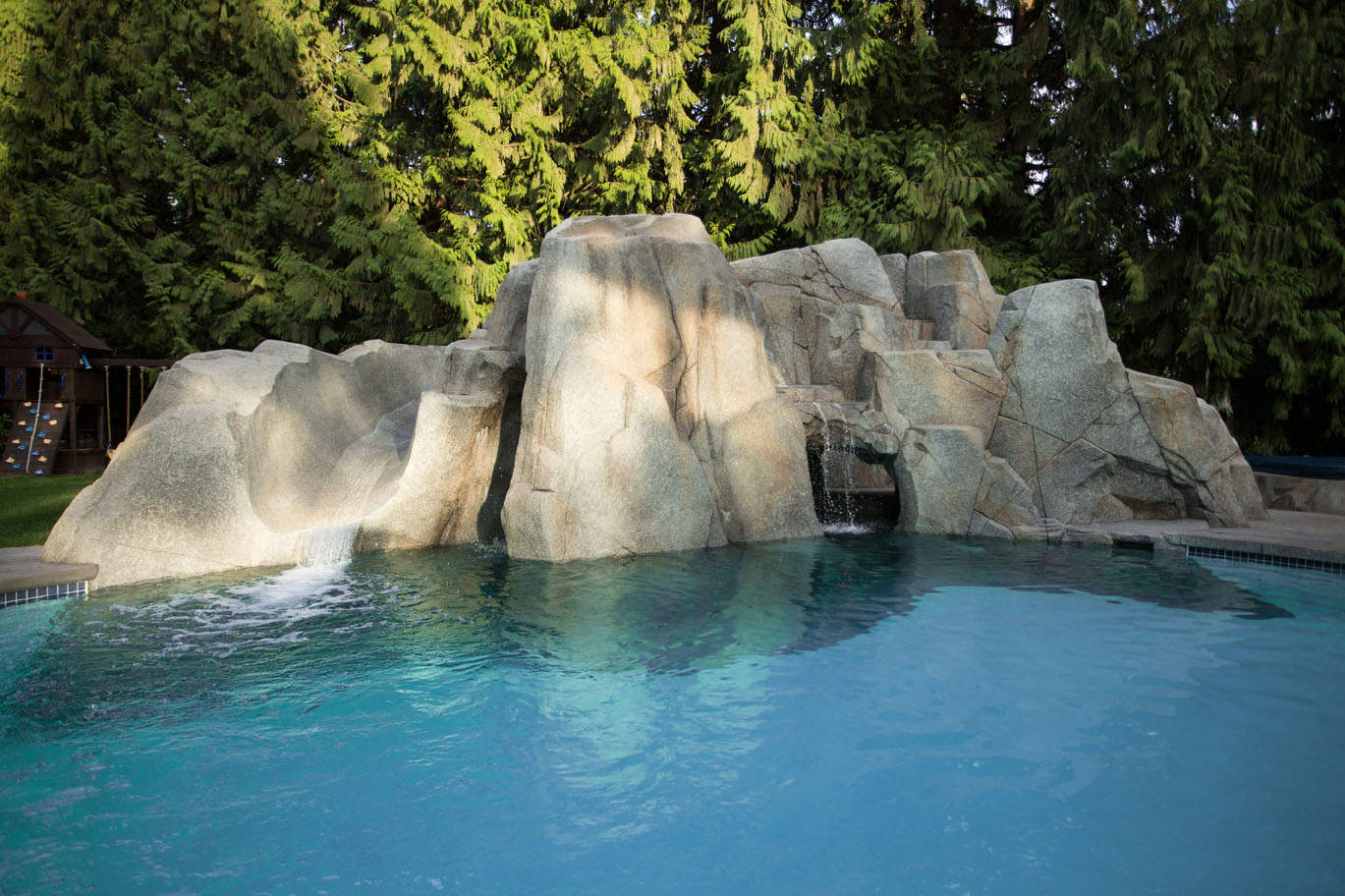 Custom in-ground pool with artificial rock and waterfalls