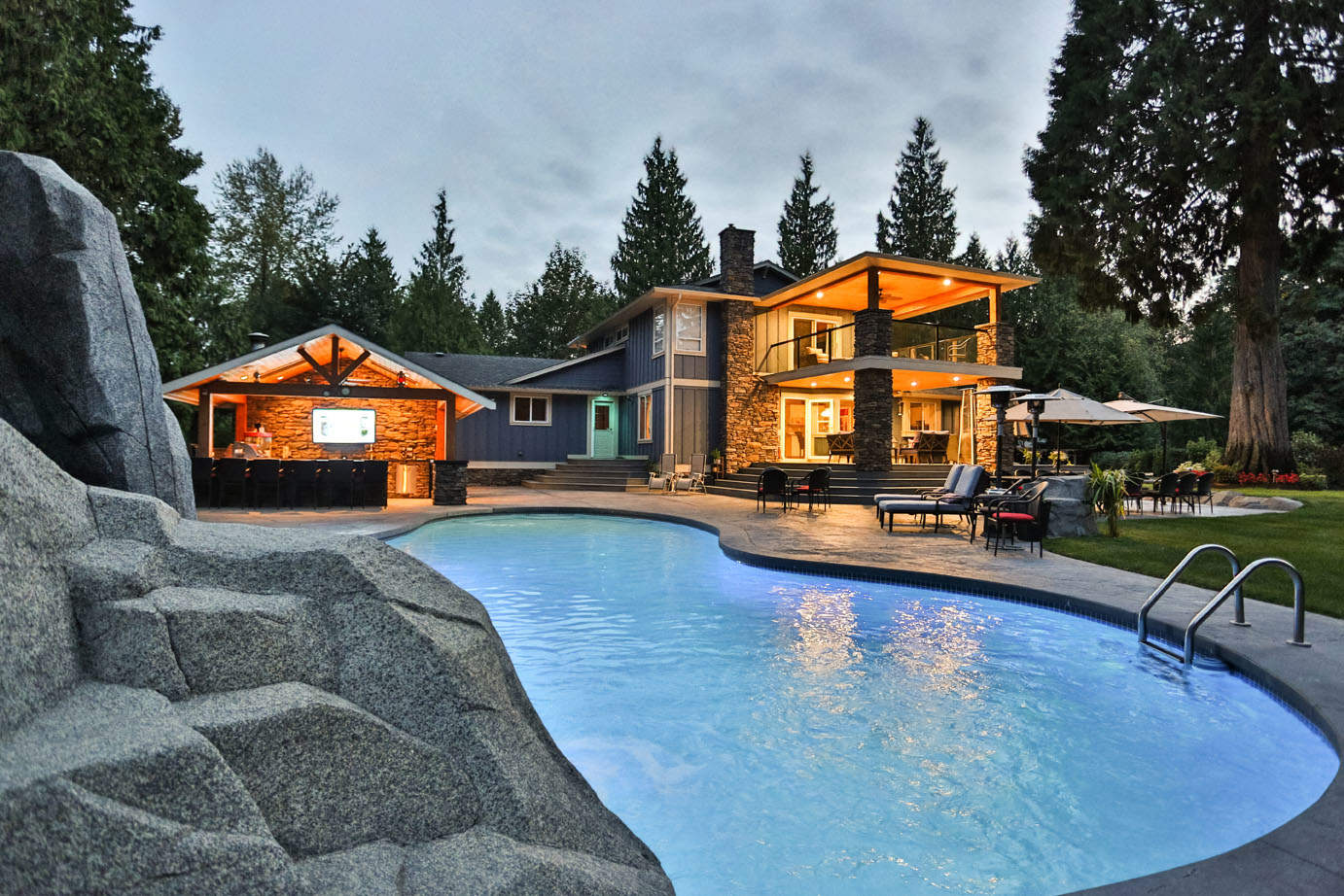 Backyard makeover with year-round kitchen, custom pool and rock work